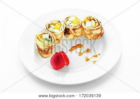 Fruit roll in pancake, kiwi, strawberry, apple, an orange on a white background