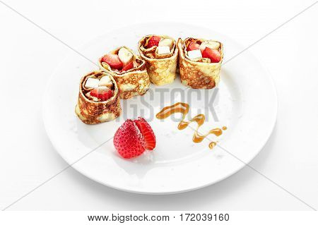 Fruit roll in pancake, strawberry, apple, on a white background
