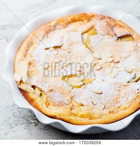Apple dutch pancake cake in a baking dish. Grey stone background