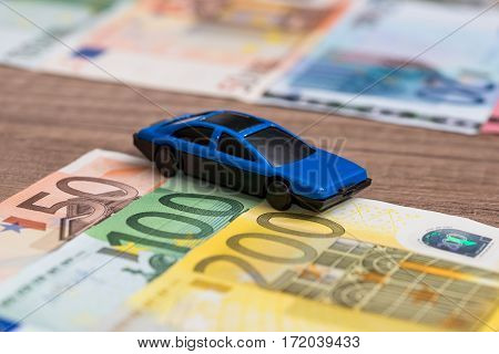 blue toy car on euro banknote close up