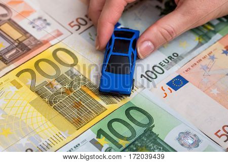 Toy car with helping hand on coin and euro banknote
