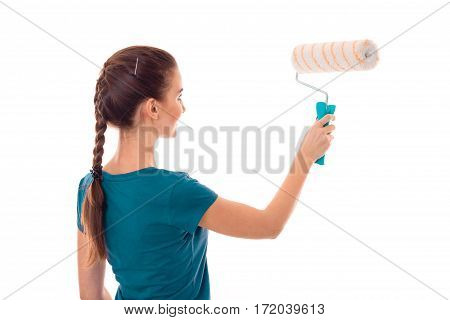 portrait of young beautiful brunette building woman in uniform with paint roller in hands makes renovation isolated on white