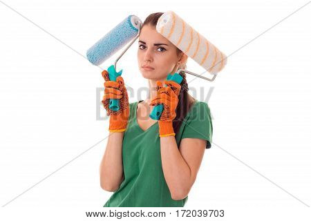 portrait of young tired brunette building woman in uniform with paint roller in hands makes renovation and looking at the camera isolated on white