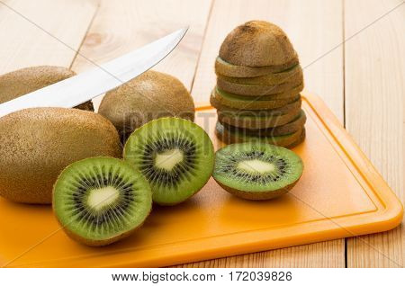 Pices Of Kiwi On Orange Chopping Board And Knife