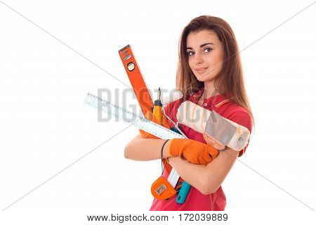 portrait of young attractive brunette building woman in red uniform with tools in hands makes renovation and looking at the camera isolated on white
