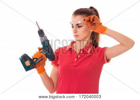 portrait of young attractive brunette building woman in red uniform with drill in hands makes renovation isolated on white