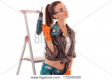 portrait of young sensual brunette building woman with closed eyes drill in hands makes renovation isolated on white