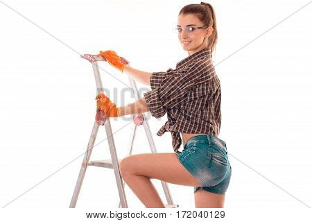 portrait of young sensual brunette building woman with ladder makes renovation and smiling on camera isolated on white