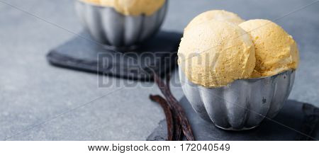 Vanilla Ice Cream with vanilla pods in metal vintage bowl. Homemade Organic product Slate background. Copy space.