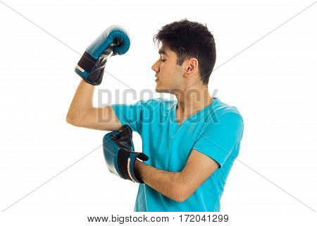 portrait of powerful brunette sports man practicing box in blue gloves isolated on white