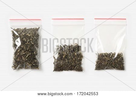 Set Of Three Empty, Half And Full Plastic Transparent Zipper Bag With Dry Green Tea Isolated On Whit