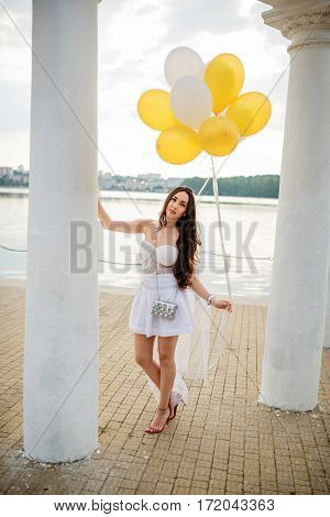 Young Brunette Girl With Balloons At Hand Weared On White Dress On Hen Party Against White Columns O