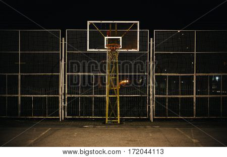 The basketball court during night view on basketball hoop and fence.