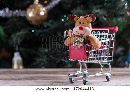 Happy Christmas raindeer sitting in shopping cart