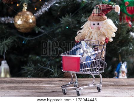 Funny Christmas character pushing shopping cart with gift