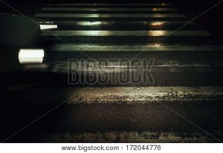 Night scene of a street crosswalk one car in motion blur on left side conceptual composition about traffic issues.