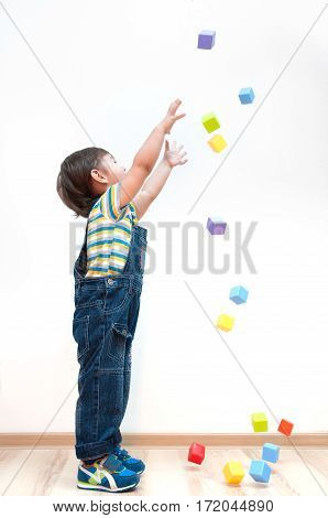 Child catching falling on top of multi-colored cubes