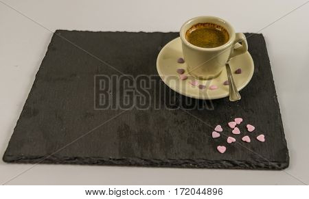 side view on small black coffee in a cup spilled sweet purple hearts black stone plate love coffee