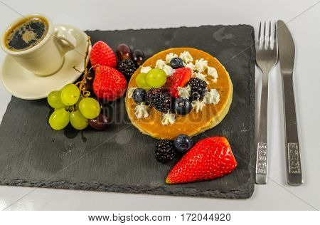 The large pancake with whipped cream and fresh fruit strawberries blueberries blackberries grapes black coffee in a cup black stone plate great dessert