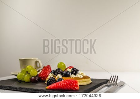 side view on large pancake with whipped cream and fresh fruit strawberries blueberries blackberries grapes black coffee in a cup black stone plate great dessert