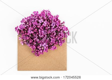 close up of opened craft paper envelope filled with spring blossom purple lilac flowers laying on white background. top view. concept of love and proposal. Flat lay. happy valentines day. womens day. 8 of march. mothers day.