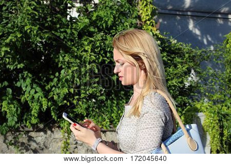 unhappy woman look at phone walking on street
