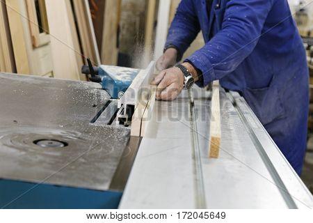 carpenter sawing wood on professional circular saw