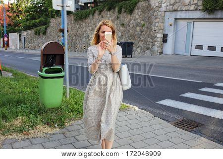 Portrait of a beautiful blond woman with trendy look using cell telephone while walking outside in summer day smiling attractive female chatting on her mobile phone near trashcan