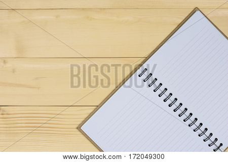 Brown notebook made from recycled open blank book pages on wooden background with copy space