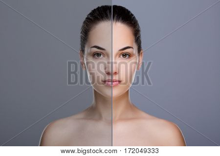 Comparison portrait of woman. Divided face of woman. One half of face with acne, before. Another half of face with retouch, after. Studio, head and shoulders, indoors. Gray background