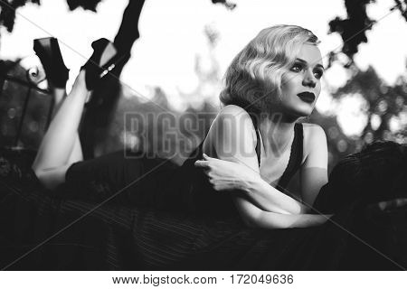 Beautiful and elegant blonde woman with red lips and hair waves wearing wine red nightie posing on the bed outdoors retro vintage style and fashion