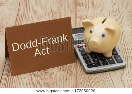 The Dodd-Frank Act A golden piggy bank card and calculator on a wood desk with text Dodd-Frank Act