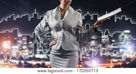 Close view of businesswoman against modern cityscape holding papers in hand