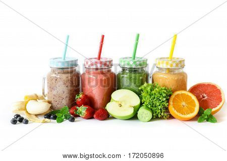 Four different smoothies in a glass jars with vegetables and fruits and ingredients on a white background isolated. Superfood detox and healthy food concept. Horizontal.