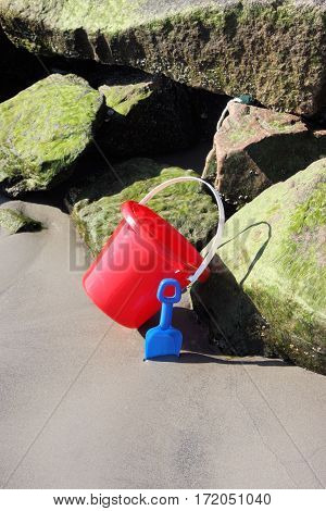 Child's beach toy pail and shovel leaning against the large rocks of a jetty at low tide.