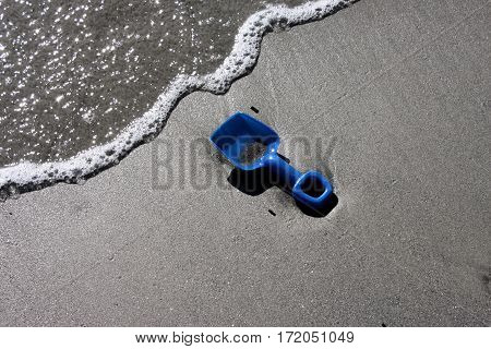 Lost blue sand shovel brought onto the beach by incoming tide.