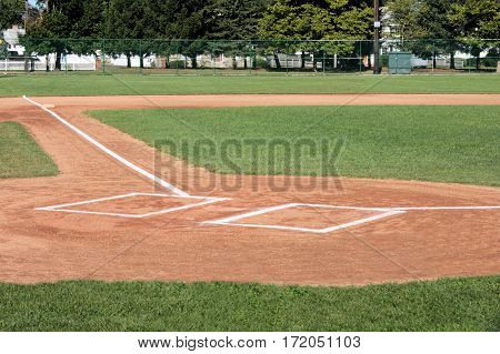 Well groomed infield, outfield, and batters box of a high school  baseball field.