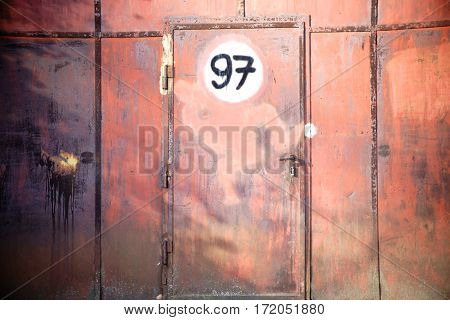 A rusted iron gate with a door and a sign.