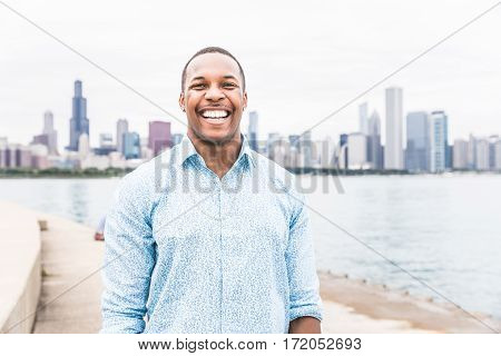 Portrait of happy black man laughing out loud in Chicago. Young man looking at camera with Chicago skyline on background. Happiness and lifestyle concepts.
