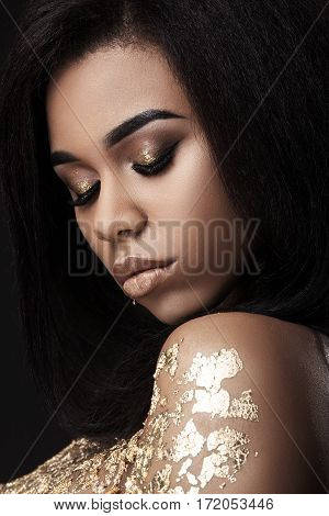 African American model with closed eyes. Body art. Dark-skinned girl, body covered with gold. Portrait. Indoors, studio, closeup