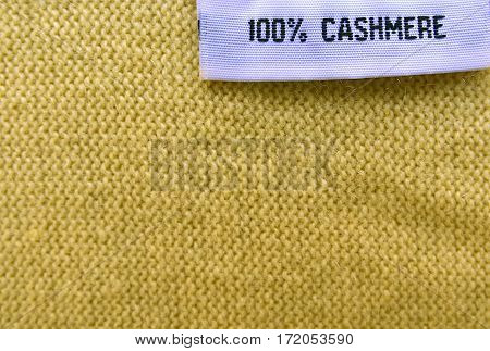 Cashmere texture.Cashmere background.100% Cashmere wool texture.Fabric label on yellow cashmere background.Selective focus.