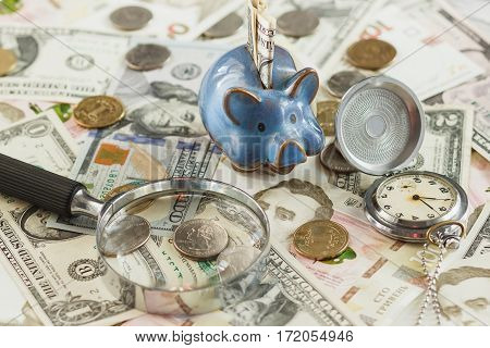Different Collector's Coins And Banknotes With A Piggy Bank And Clock