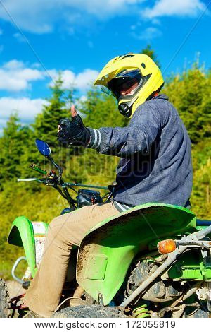 racer with yellow helmet on green quad enjoying his ride outdoors, showing OK gesture