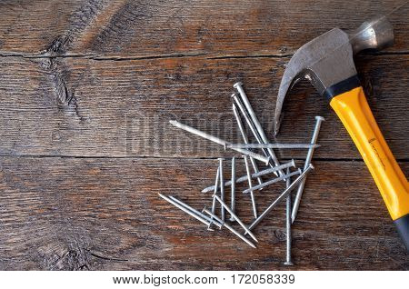 A top view image of an old used yellow hammer and a pile of nails on a wooden workbench.