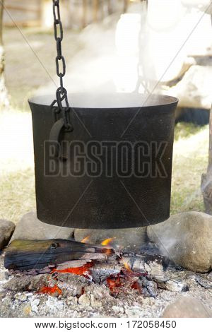 Old black pot on fireplace, chain, stones