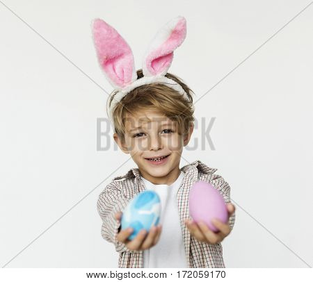 A boy is holing easter eggs and put pink bunny ear on.
