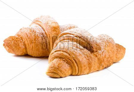 two croissant sprinkled with powdered sugar isolated on a white background closeup.