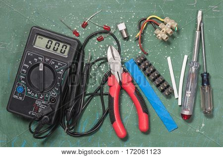 A set of electrical components and tools on a green background