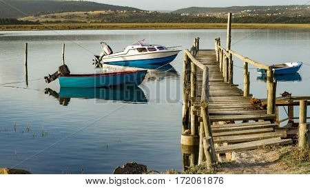 Three boats lie moored to the wooden jetty in the lower parts of the river.