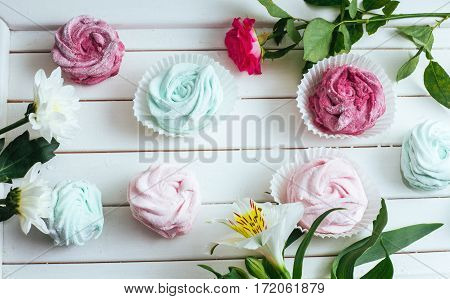 Rose marshmallows and beautiful flowers on a white background wood.